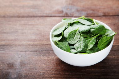 Spinach leaves in bowl on brown wooden table