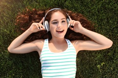 Young woman with headphones lying on green grass in the park