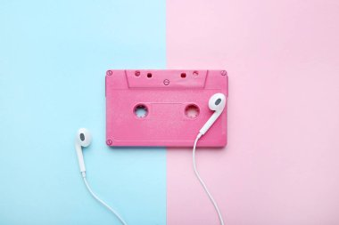 Cassette tape with earphones on blue and pink background