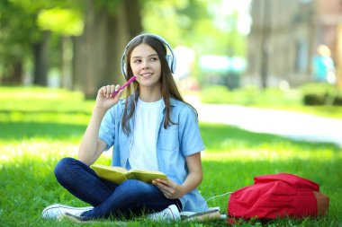 Cute girl sitting with book and headphones in the park