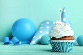 Cupcake with candle, paper caps and balloon on blue background