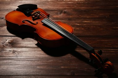 close-up of violin on brown wooden background