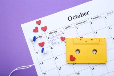 Yellow cassette tape with paper october calendar on purple background