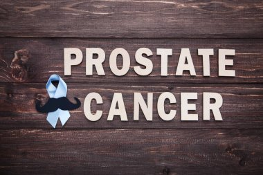 Blue ribbon with inscription Prostate Cancer on wooden background