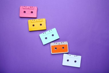 Colorful cassette tapes on purple background