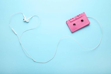 Cassette tape with earphones on blue background