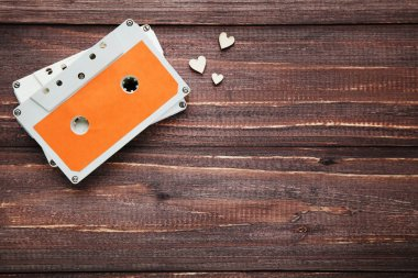 Cassette tape and small hearts on brown wooden background
