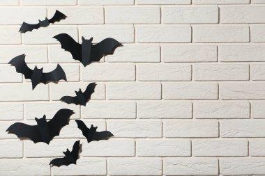 Halloween paper bats on white brick wall background