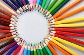 Barevné tužky v kruhu na šedém pozadí