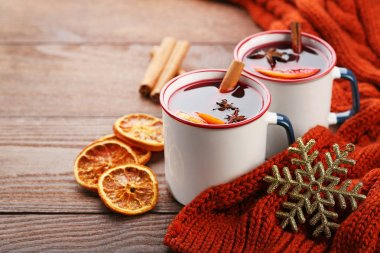 Mulled wine in mugs with scarf on wooden table