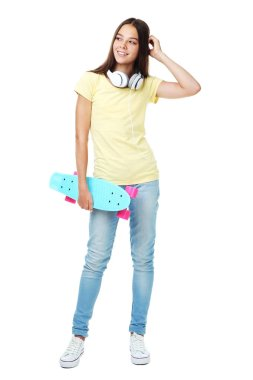 Young girl with skateboard and headphones on white background