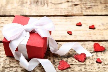 Şerit yay ve kalpleri kahverengi ahşap masa üzerinde hediye kutusu