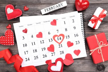 Valentine day calendar with red hearts and gift boxes on wooden table stock vector