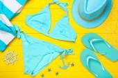 Módní plavky s oděvy na žlutém dřevěném stole