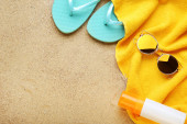 Flip flops with sunglasses and moisturizer cream on beach sand