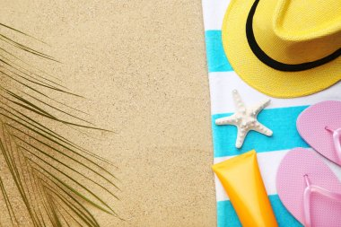 Flip flops with starfish, palm leaf and hat on beach sand stock vector