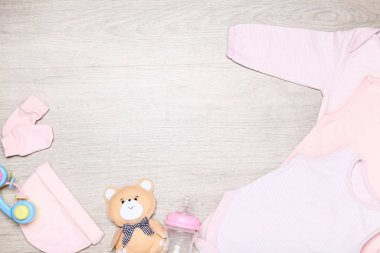 Baby clothes with toys and bottle on the floor