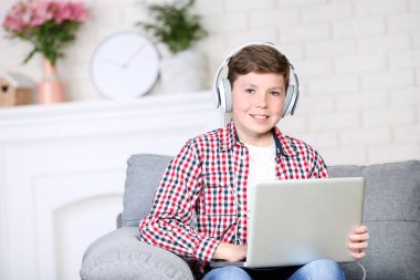 Young boy with laptop and headphones sitting on sofa