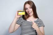 Mladá žena držící kreditní kartu na šedém pozadí