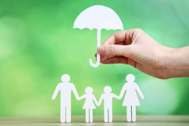 Family figures and female hand holding paper umbrella on green background stock vector