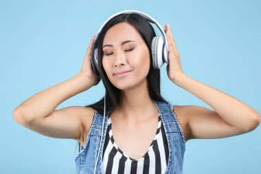 Beautiful woman with headphones on blue background