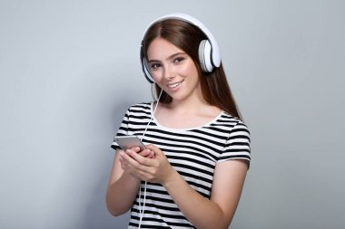 Young woman with headphones and mobile phone on grey background
