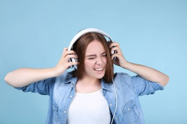 Young beautiful woman with headphones on blue background