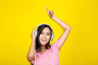 Beautiful woman with headphones on yellow background