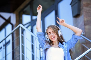 Young beautiful girl listening music with headphones