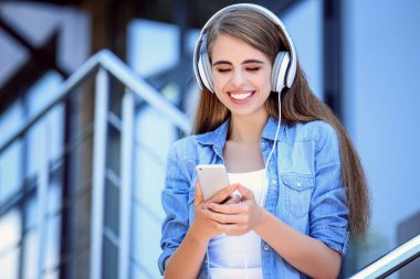 Young beautiful girl listening music with headphones and using s