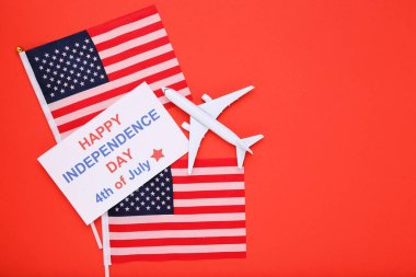 Text Happy Independence Day with flags and airplane model on red background