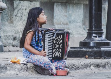 Oaxaca, Oaxaca / Mexico - 21/7/2018: (Little girl playing the accordion in downtown Oaxaca Mexico)