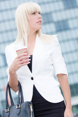 Young blonde business woman outdoor with a paper cup of coffee