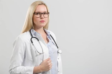 Female friendly young family doctor in doctor's overall with ste