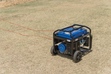 Top view gasoline powered portable generator sunny day. Outdoor power equipment standby, mobile backup generator for disaster recovery or construction.