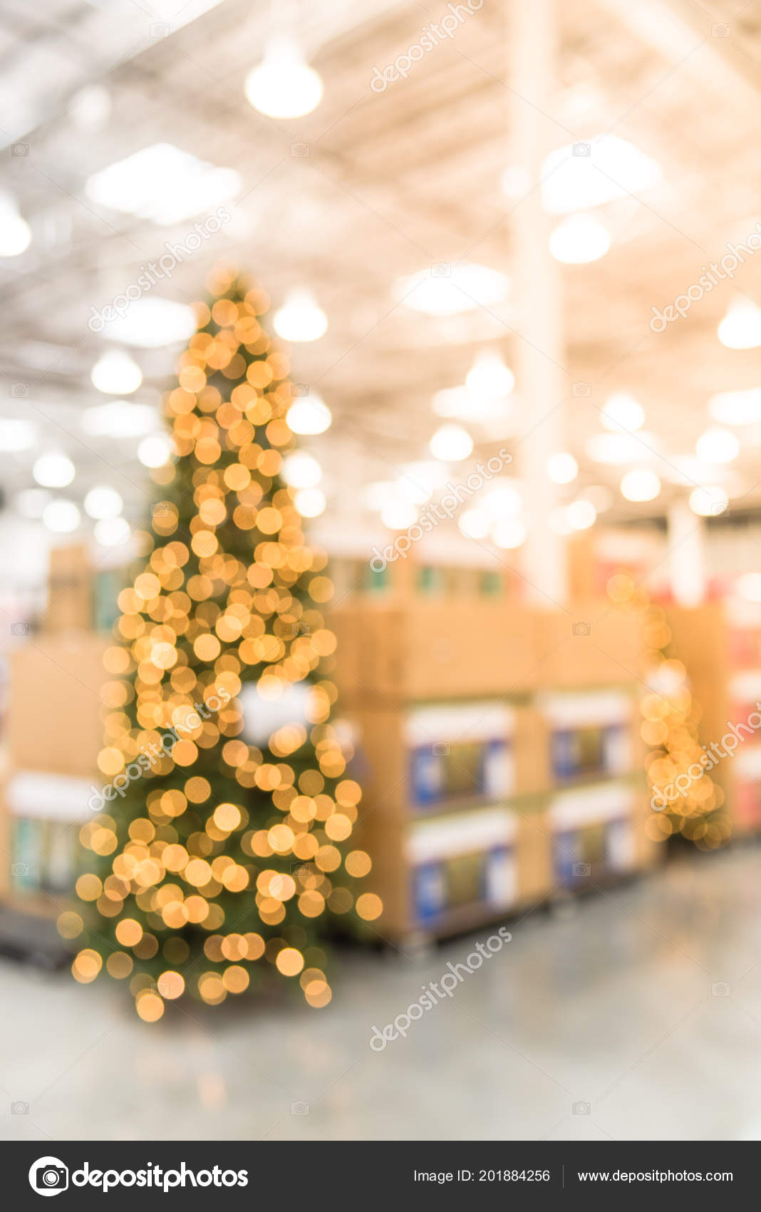 Blurred image huge Christmas tree decoration in wholesale store. Wreaths and strings of bokeh lights surround the artificial Christmas tree.