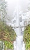 Photo Close-up bridge and top tier full 542-foot height of Multnomah Falls in winter time. Natural and seasonal waterfall background
