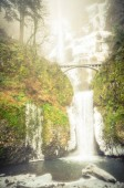 Photo Vintage tone beautiful pedestrian stone bridge and knee-wobbling vantage point over the second tier 69-foot drop of Multnomah Falls lower in winter time. Natural and seasonal waterfall background