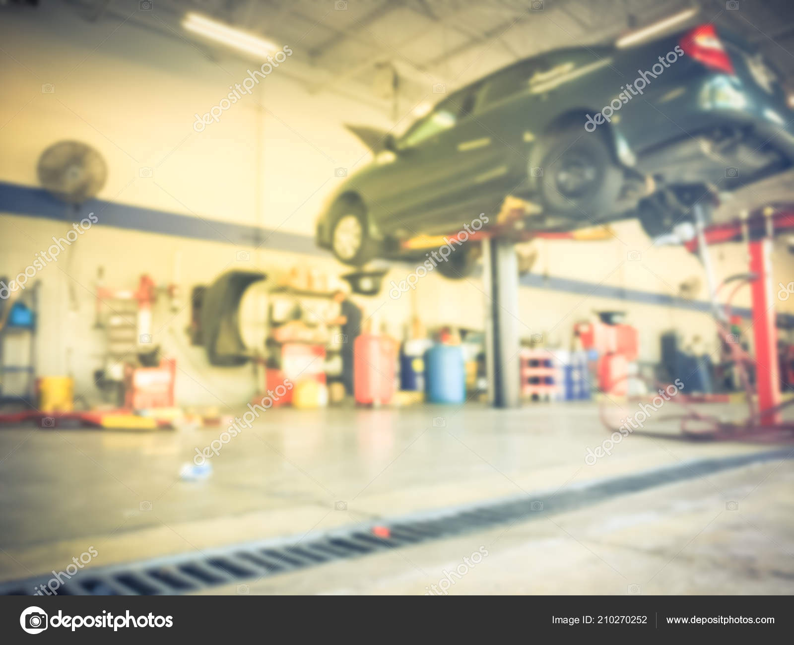 Motion Blurred Abstract Mechanic Changing Oil Lifted Car Auto Shop