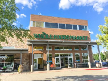 DALLAS, TX, US-SEPT 2, 2018:Customers enter facade entrance of Whole Foods Market store on sunny morning. Eco-minded supermarket chain featuring food without artificial preservatives, colors, flavors