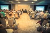 Vintage-Ton verschwimmt Business-Seminar-Meeting mit LED-Projektor Bildschirm, Redner-Rede auf der Bühne. defokussiertes Publikum im Konferenzsaal, das Talkshows lauscht. Bildung, Geschäftskonzept