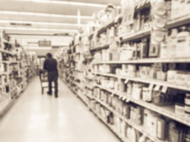 Vintage tone blurred motion customer with cart shopping for personal care as hair accessories, shampoo, hair care, cosmetics, bar soap, feminine care at grocery store with price tags in Texas, America