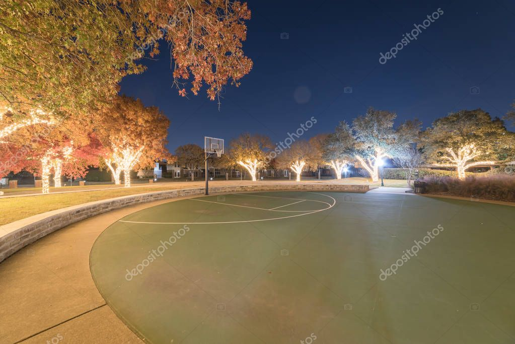 Illuminated holiday lightings at public park with basketball cou