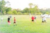 Rozmazaně na pozadí fotbal s klukama Latinské Ameriky v parku během západu slunce