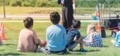Panoramatický výhled dozadu multikulturní děti na travní louce z venkovní hry