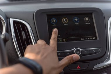 Asian man hand with smart watch touching screen in modern car