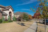 Fotografie Typischer Vorbau-Eingang neuer Vorstadthäuser mit geparkten Autos auf der bunten Herbststraße außerhalb von Dallas, Texas, USA