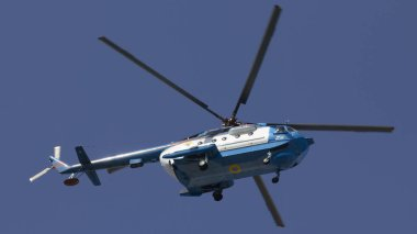 Military helicopter maneuvers in the blue sky.