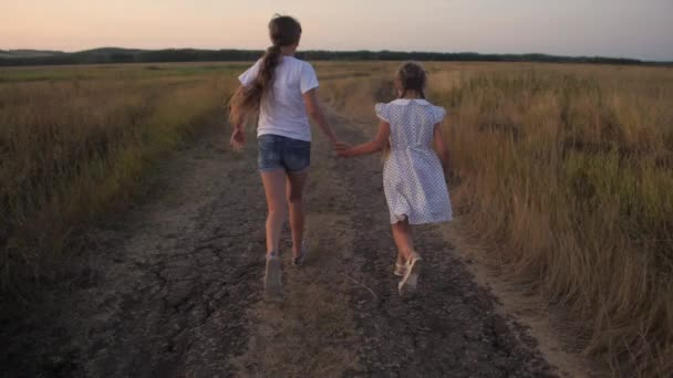 Girls teenagers run along road in field. Slow motion.