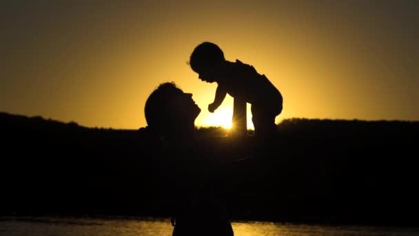 Mutter wirft ein Baby, das bei Sonnenuntergang spielt. Zeitlupe.